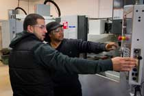 Accelerated precision tooling certificate program students operate a CNC machine