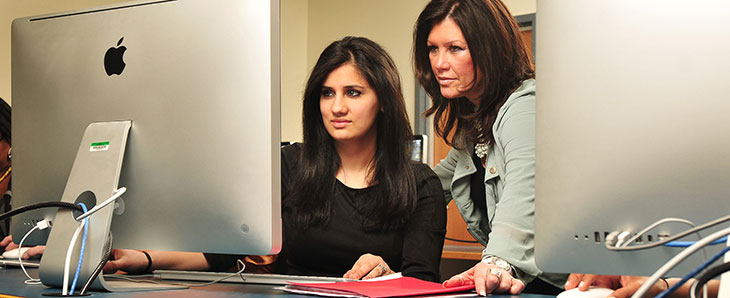 student at a computer being helped by a support person