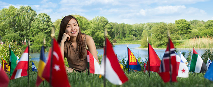 Student sitting in grass near flags.