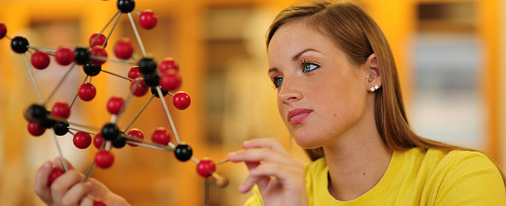 Photo of student working on model of molecules