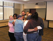 student employees engaging in a group hug