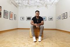 Photo of a male sitting in an art gallery