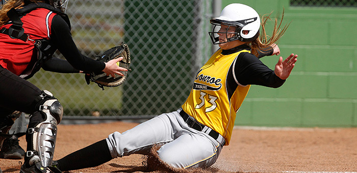 Photo of MCC Lady Tribune softball player sliding into home plate.